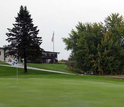 A view of a hole with clubhouse in background at River Edge Golf Course