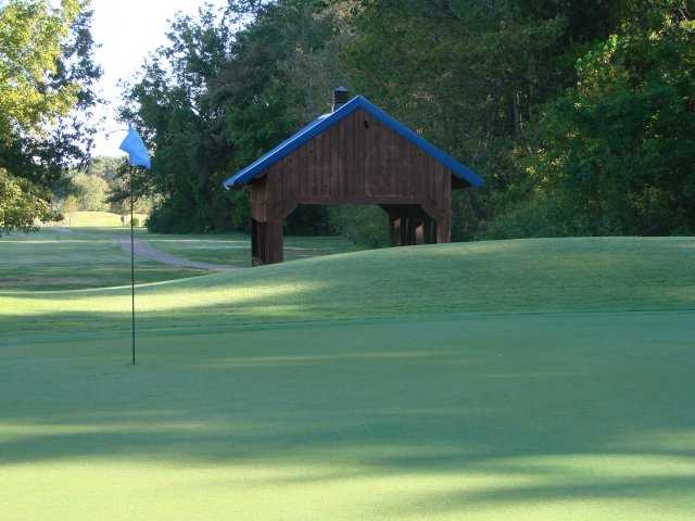 A view of a hole with a narrow road in background at Timber Truss Golf Course.