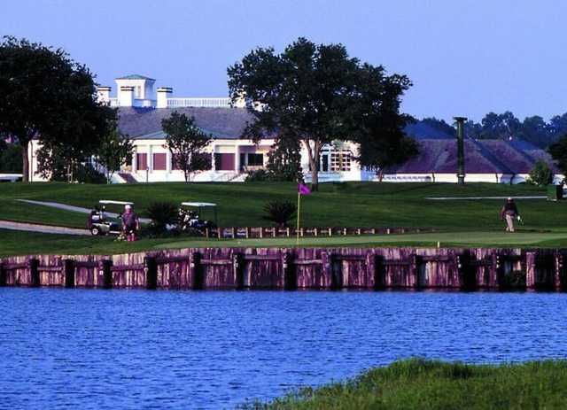 A view over the water of a green and the clubhouse at English Turn Golf & Country Club