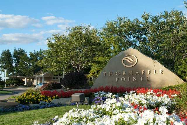 A view of Golf Club at Thornapple Pointe sign and clubhouse in background