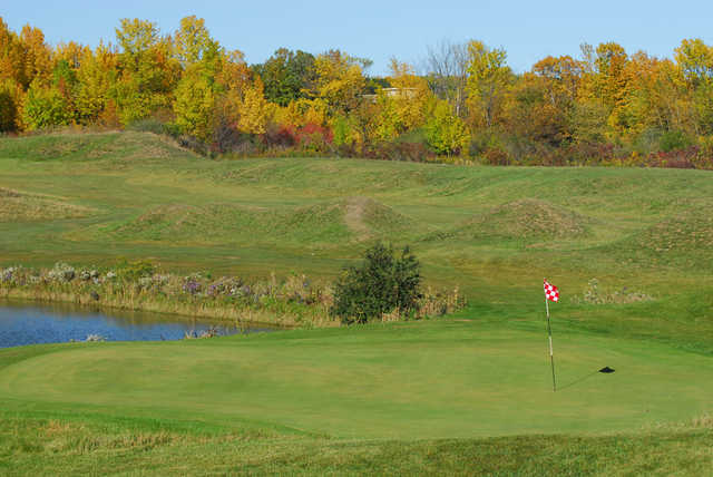 A fall view of a hole with water coming into play from left at Missing Links Golf Course