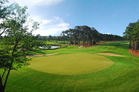 A view of a green protected by bunker at Pine Lakes Country Club.