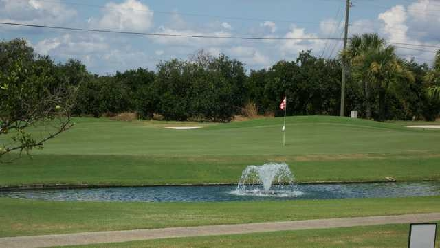 A view of a hole at River Greens Golf Course with water fountain in foreground