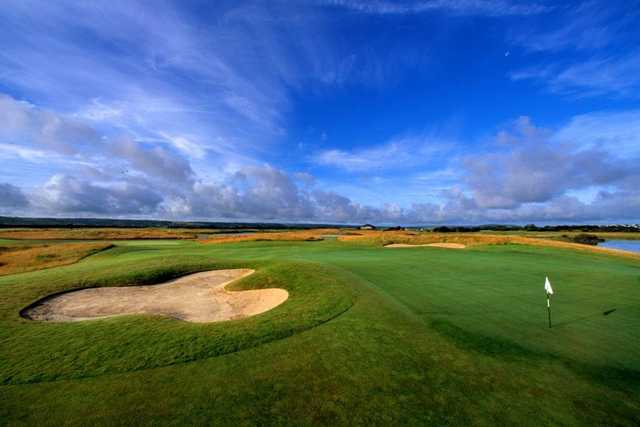 A view of a green guarded by bunker at Machynys Peninsula Golf & Country Club