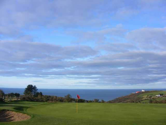 A view of green with water in background at Aberystwyth Golf Club