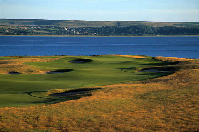 A view of a hole with water in background at Machynys Peninsula Golf & Country Club