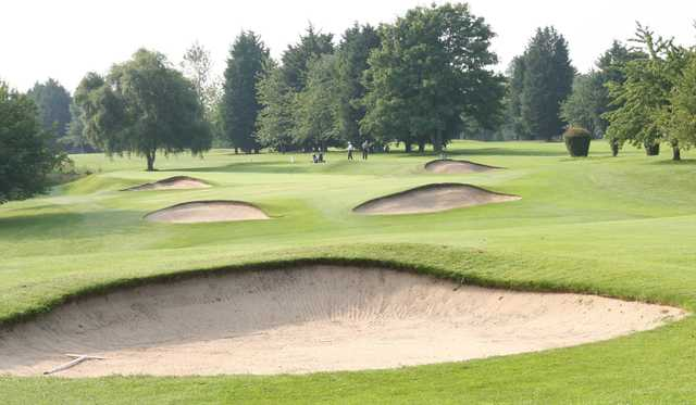 A view of a green protected by bunkers at Flackwell Heath Golf Club.