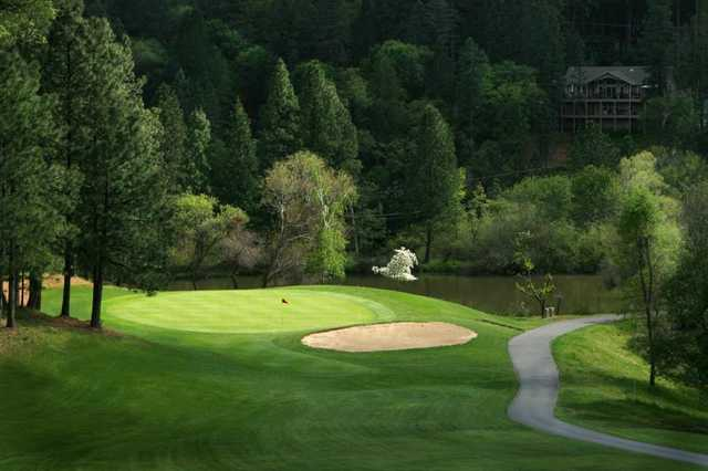 A view of green guarded by bunker at Alta Sierra Country Club