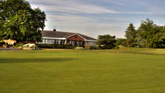 A view of the clubhouse with green in foreground at Crewe Golf Club