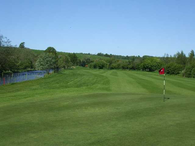A view of green and fairway with water on the left side at Carus Green Golf Club