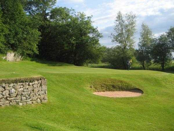 A view of green #8 guarded by bunkers at Grange-over-Sands Golf Club