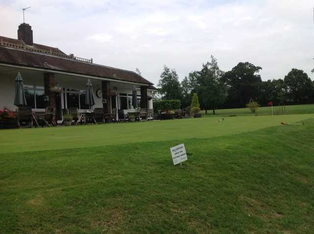 A view of the putting green and clubhouse at Grims Dyke Golf Club