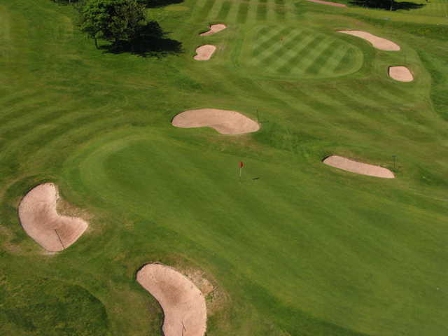 Aerial view of green protected by bunkers at Saddleworth Golf Club