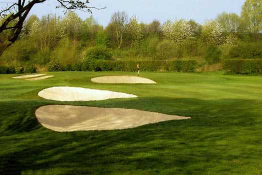 A view of a hole guarded by bunkers at Withington Golf Club