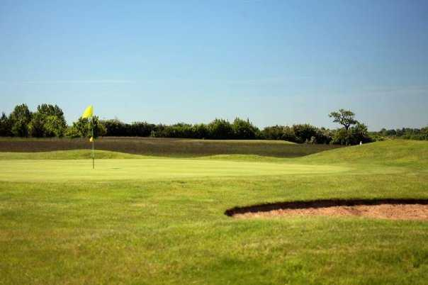 A sunny view of a green guarded by bunker at Championship Course from Great Hadham Golf Club