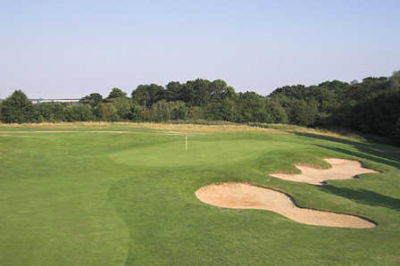 A view of a green protected by sand traps at Hertfordshire Golf Club