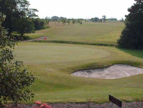 A view of a green guarded by sand traps at Mossock Hall Golf Club