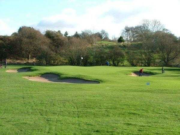 A view of the 15th green guarded by bunkers at Penwortham Golf Club