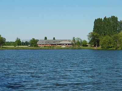A view over the water of the clubhouse at Beedles Lake Golf Centre