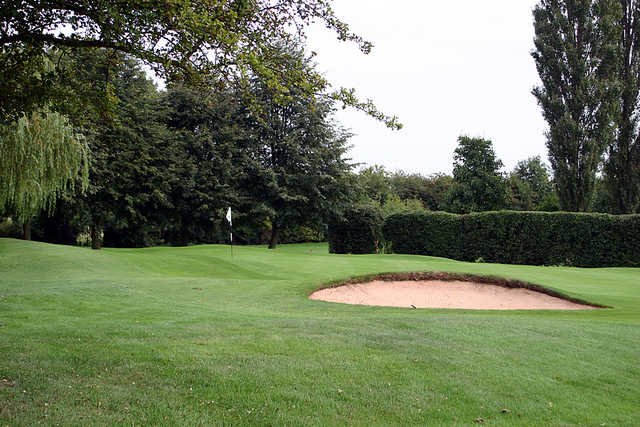 A view of a green guarded by bunker at Birstall Golf Club