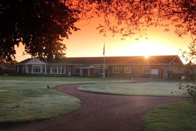 Holme Hall clubhouse set against a sunset backdrop