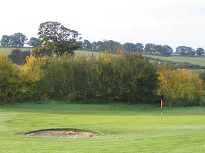 A view of the 1st green guarded by bunker at Rothbury Golf Club