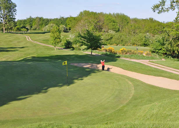 A view of a green with narrow path on the right side at Taunton & Pickeridge Golf Club