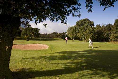 A view of a green protected by bunker at Dore & Totley Golf Club
