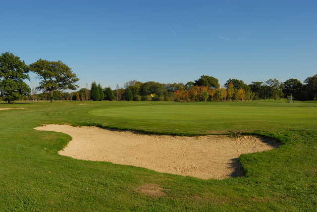 A view of a green protected by sand trap at Horne Park Golf Club