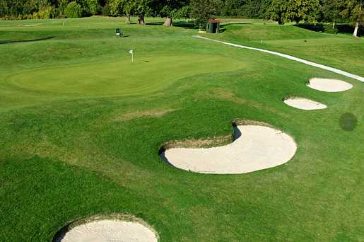 A view of a green protected by a collection of bunkers at Reigate Hill Golf Club