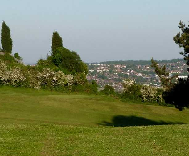 A view from a fairway with spring blossom trees protecting a green at Dudley Golf Club