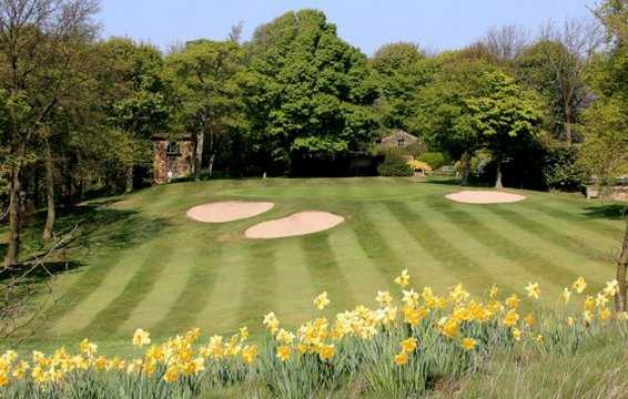 A view of the 11th green protected by a collection of bunkers, with spring flowers in foreground at Huddersfield Golf Club
