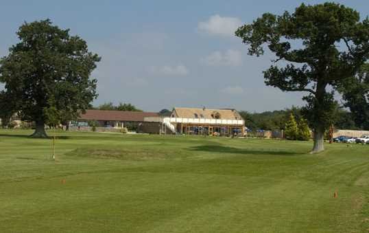 A view from a tee with the clubhouse in background at Oaksey Park Golf & Leisure Club