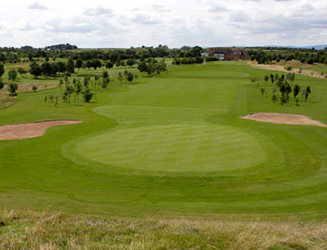 A view of a green guarded by sand traps at Lenches Course from Vale Golf & Country Club