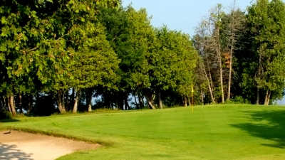 A view of a green protected by bunker at Island Brae Golf Club