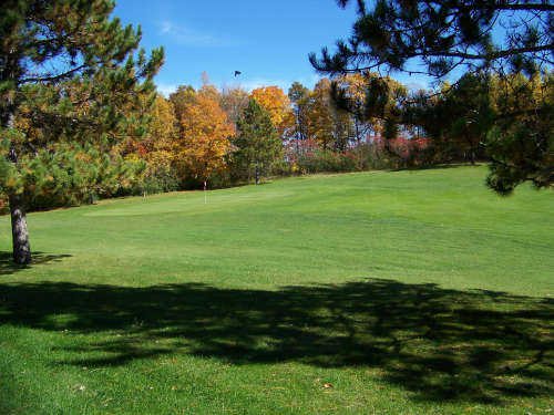 A view from a fairway of a green guarded by colorfull fall trees at Tianna Country Club