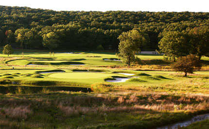 A view of a green surrounded by a collection of bunkers at Bedford Springs Old Golf Course