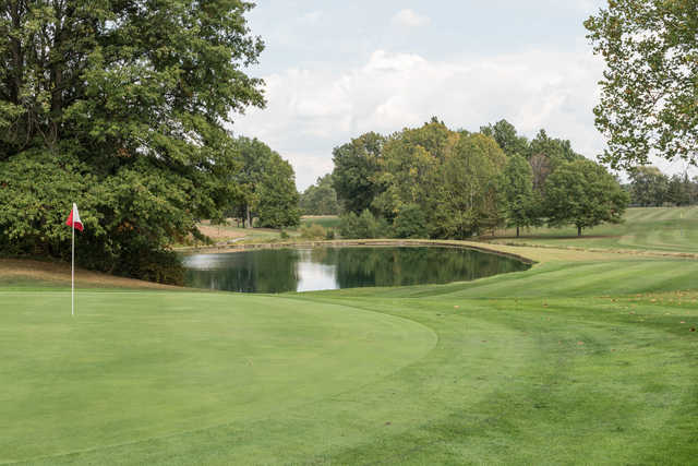 A view of a green with water in background at Pine Brook Golf Links.