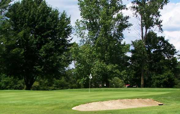 A view of a green protected by bunkers at Leaning Tree Golf Club