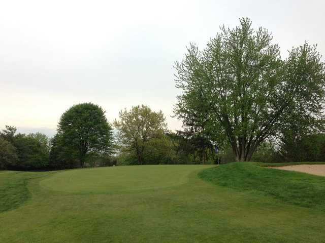 A view of a green protected by a bunker at Georgetown Country Club