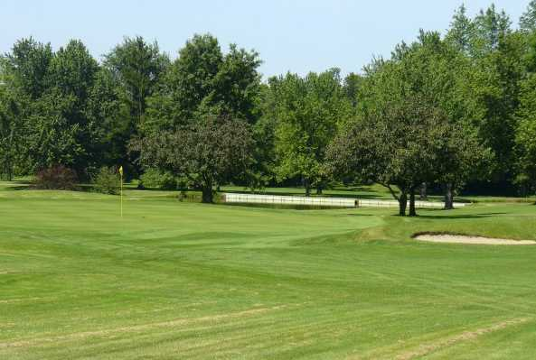 A view of a green guarded by a bunker at Shelby Country Club