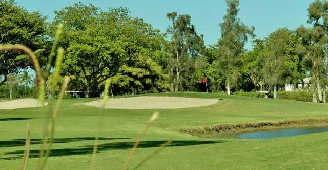 A view of a green protected by sand traps and a pond at Villa Del Ray Golf Club
