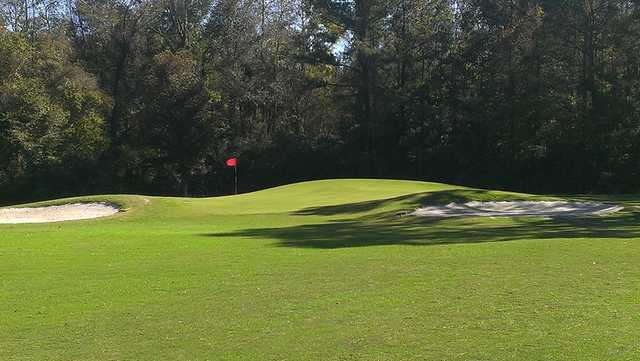 A view of a green protected by tricky bunkers at Holly Hill Golf Club