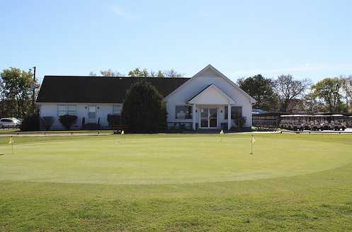 A view of the clubhouse and practice putting green in foreground at Hunters Point Golf Club