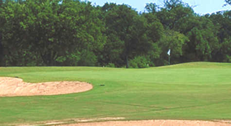 A view of a green protected by a bunker at Sycamore Creek Golf Course
