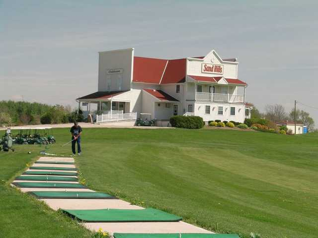 A view of the driving range tees and the clubhouse in the distance at Sand Hills Golf Resort