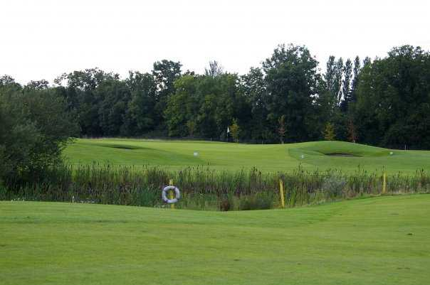 A view over a pond of the 4th green at Grange Castle Golf Club