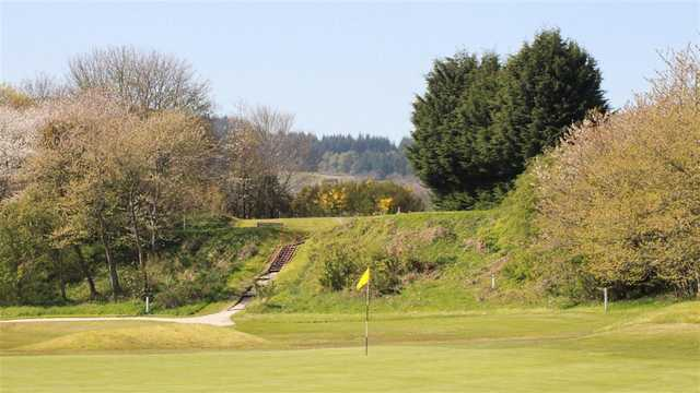 A view of a green with a narrow path on the left side at Torvean Golf Club