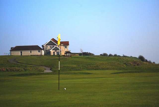 A view of a hole with a narrow path to the clubhouse in background at Ashburnham Golf Club