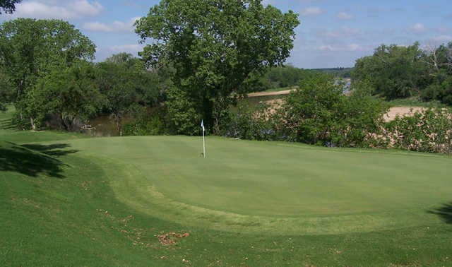 A view of an undulating green with water in background at SugarTree Golf Club
